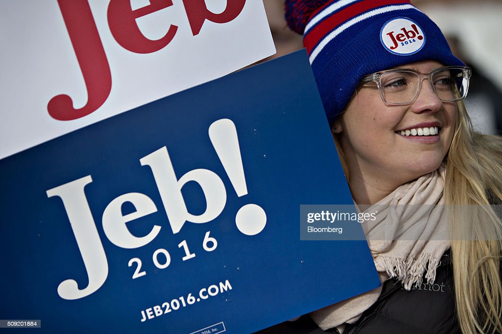 A volunteer for the campaign of Jeb Bush, former governor of Florida and 2016 Republican presidential candidate, not pictured, holds a sign outside a polling station in Bedford, New Hampshire, U.S., on Tuesday, Feb. 9, 2016. Voters in New Hampshire took to the polls today in the nation's first primary in the U.S. presidential race. Photographer: Daniel Acker/Bloomberg via Getty Images
