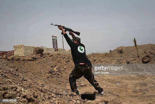 A volunteer from the Badr Brigade militia fires on ISIS fighters from the frontline on April 11 2015 in Ebrahim Ben Ali in Anbar Province Iraq Shia...