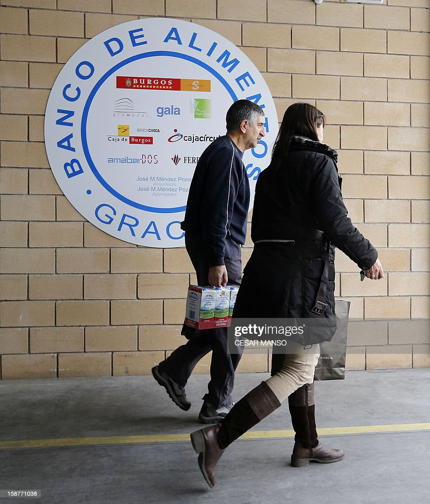 A volunteer from the Food Bank and Social Agent carry food donated by individuals, supermarkets and wholesalers in the national campaign to fight hunger in Spain in the warehouse of the Food Bank of Burgos in northern Spain on December 27, 2012. The Spanish Federation of Food Banks, established in 1987 in Barcelona to be retrofitted in all provinces of the country, last year distributed 104 million kilos of food for free. AFP PHOTO/ CESAR MANSO