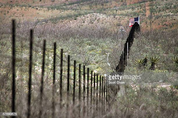 A volunteer from the Minuteman Project stands near an American flag placed in the barbed wire fence which divides the US/Mexican border April 4 2005...