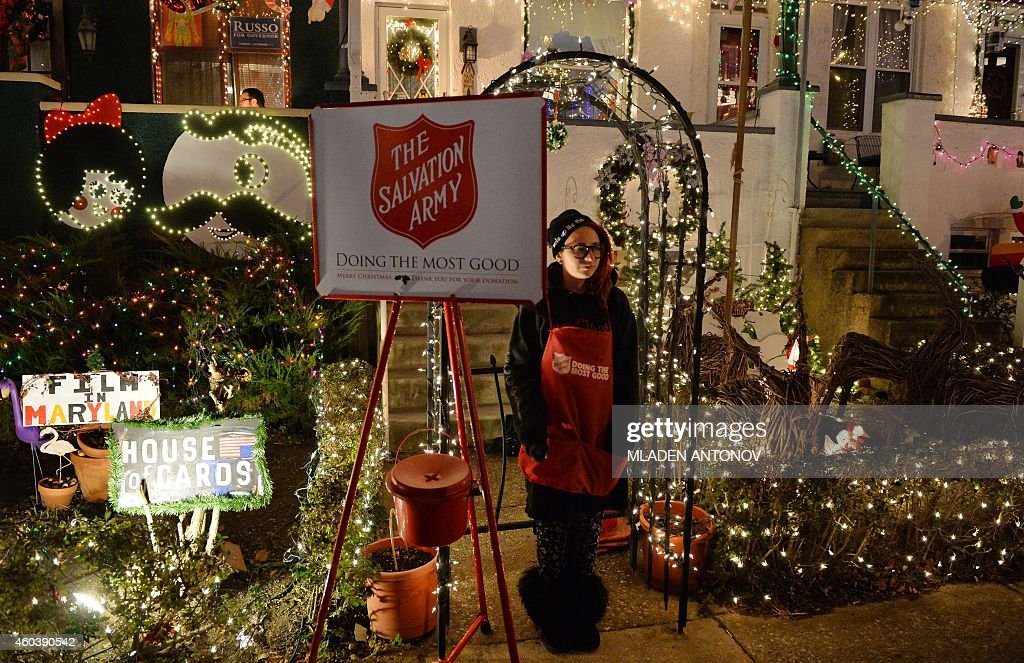 A volunteer from the Salvation Army collects money in front of a house illuminated for Christmas on the 700 block of 34th Street in the Hampden...