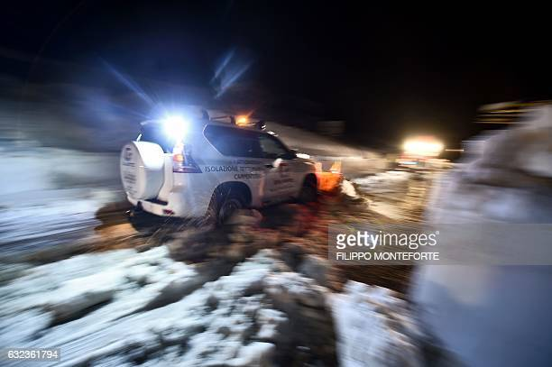 TOPSHOT A volunteer from Ticino Switzerland clears the road with his own car snow plow in the village of Castelli some 15 km from the site where an...
