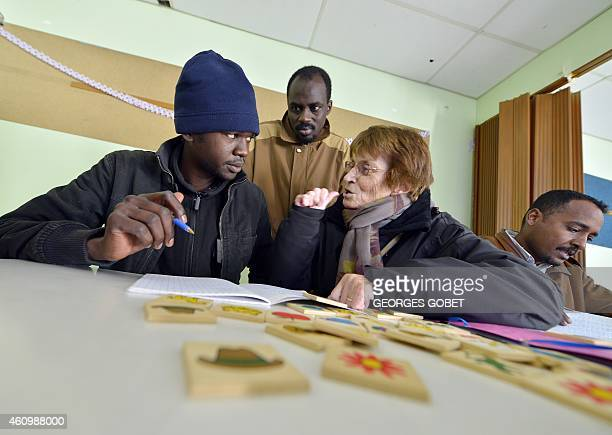 A volunteer gives a French lesson to a migrant seeking asylum in a presbytery in the SainteMariedeDoulon's parish in Nantes western France on...
