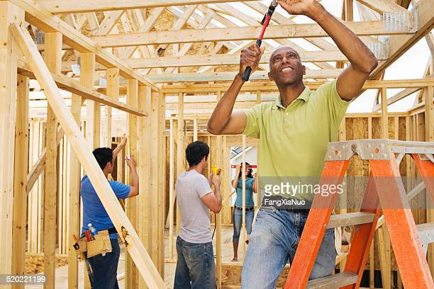 Volunteer hammering nail into wooden home construction