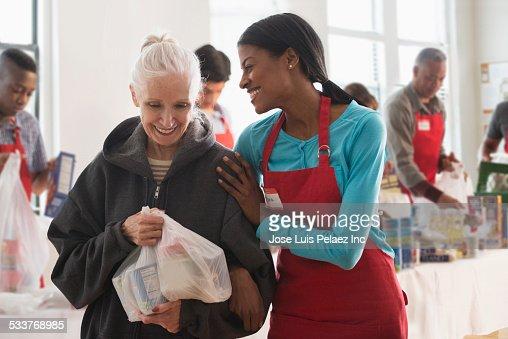 Volunteer handing out food at food drive