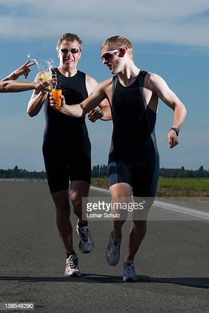 A volunteer handing water to runners in a race