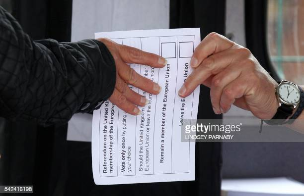 A volunteer hands an unmarked ballot paper to a voter inside a bus being used as a temporary polling station in KingstonUponHull northern England on...