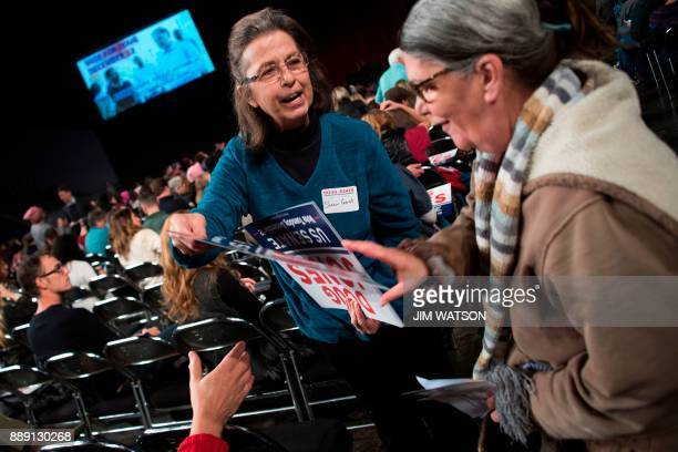 A volunteer hands out Democratic Senatorial candidate Doug Jones placards as they prepare for a rally in Birmingham Alabama on December 9 2017 The...