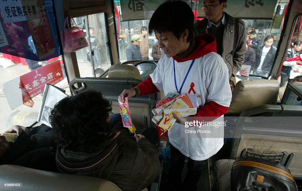 A volunteer hands out leaflet to a passenger on a coach during an AIDS awareness promotion held to mark the World AIDS Day on December 1, 2008 in Chengdu of Sichuan Province, China. According to official estimates, China has 700,000 people living with HIV with an estimated 85,000 with AIDS.