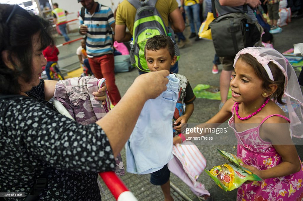 A volunteer hands over clothes to migrant children who had arrived at Munich Hauptbahnhof main railway station on September 1, 2015 in Munich, Germany. Over a thousand migrants arrived in southern Germany by train in the last 24 hours, many of them who boarded trains in Budapest. According to police hundreds of migrants are arriving in southern Germany daily, either via people smugglers from Hungary along the A3 highway or via trains coming from Italy. Germany is expecting to receive 800,000 asylum-seeking migrants this year and is struggling to cope with the record number.