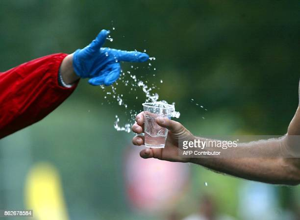 A volunteer hands over some water to a runner during the 29th Berlin Marathon 29 September 2002 AFP PHOTO DPA/WOLFGANG KUMM/wk dt fob / AFP PHOTO /...