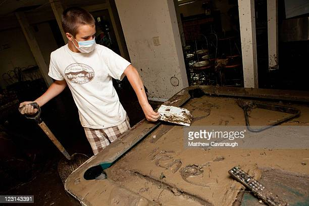 Volunteer Hank Sweeney cleans up a muddy pool table at The Crafts Inn on West Main Street where Tropical Storm Irene caused severe flooding in the...