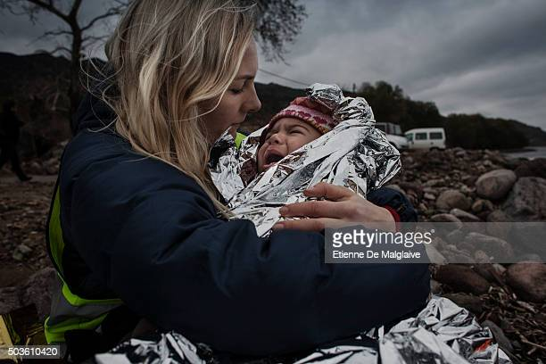 A volunteer helper comforts a crying baby as its family wait for transportation to a transit camp after they arrived in rubber boats on the shores of...