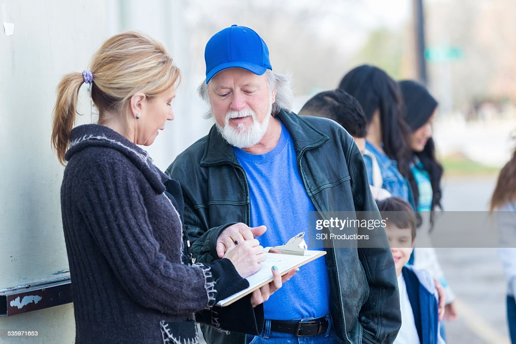 Volunteer helping families in line at neighborhood food bank : Stock Photo
