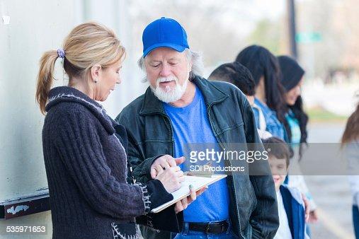 Volunteer helping families in line at neighborhood food bank : Stock Photo