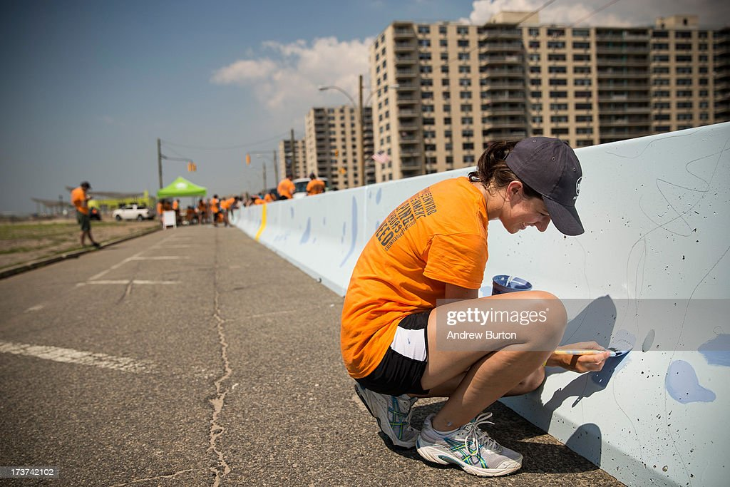 A volunteer helps painted a mural along a roadway barrier on July 17, 2013 in the Rockaway neighborhood of the Queens borough of New York City. The project, which was put together by New York City Parks, invited artists to submit visions for how to reimagine ordinary objects in an effort to re-vamp the Superstorm Sandy damaged neighborhood.