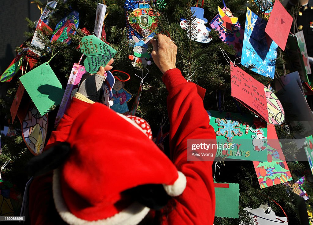 A volunteer helps to decorate a Christmas tree at the Vietnam Veterans Memorial December 19, 2011 in Washington, DC. The Vietnam Veterans Memorial Fund (VVMF) honored veterans and active-duty military personnel during its annual Christmas tree ceremony by placing the tree, decorated with homemade holiday greeting cards and ornaments sent by Americans, near the wall of the memorial.