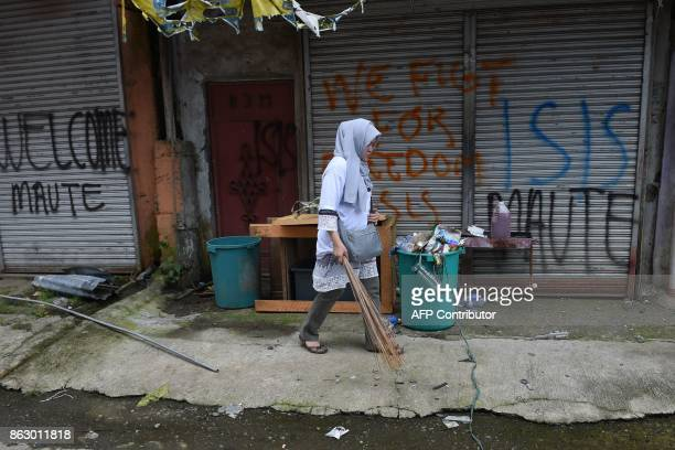 A volunteer holding a broomstick walks past graffiti on a wall as local government employees and volunteers held a cleanup drive in safe zones as...