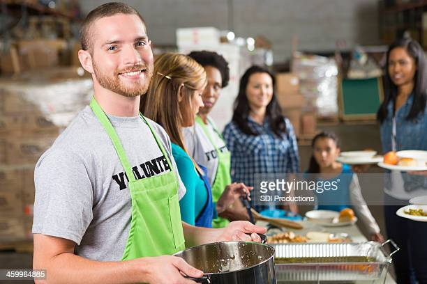 Volunteer holding soup pot at community outreach kitchen