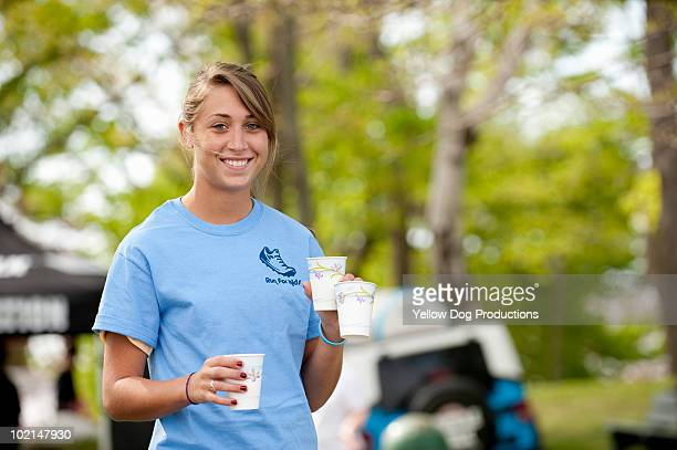 Volunteer holding water for race participants
