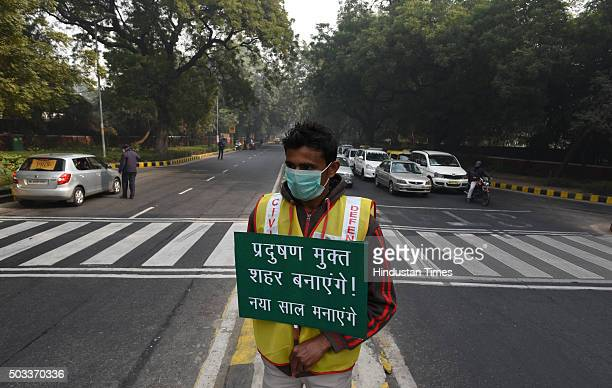 A volunteer holds a placard for pollution free capital at APJ Kalam crossing during the Delhi's oddeven traffic arrangements on January 4 2016 in New...