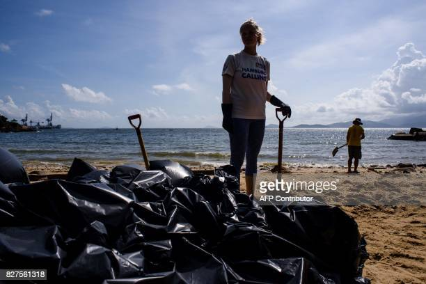 A volunteer holds a shovel in front of black bin bags as she helps remove washed up palm oil from a beach on Hong Kong's outlying Lamma Island on...