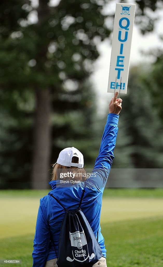 A volunteer holds up a 'Quiet eh' sign on the third hole during the first round of the Shaw Charity Classic on August 29, 2014 in Calgary, Canada.