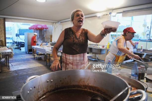 A volunteer in the kitchen prepares pasta and gnocchi with tomato sauce at the Festa dell'Unita after Italian politician Matteo Renzi Secretary of...