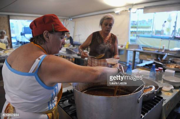 A volunteer in the kitchen prepares pasta with tomato sauce at the Festa dell'Unita after Italian politician Matteo Renzi Secretary of the Democratic...