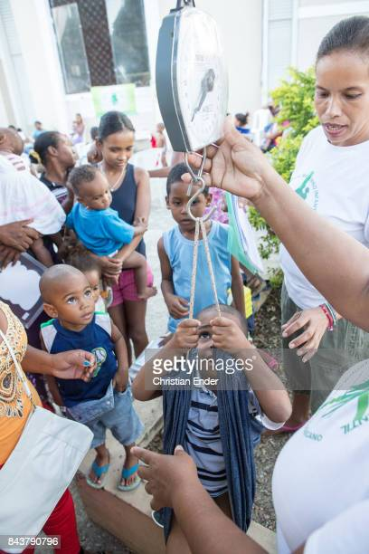 Santa Domingo Dominican Republic November 30 2012 A volunteer is checking the weight of a toddler while several other mothers are waiting with their...