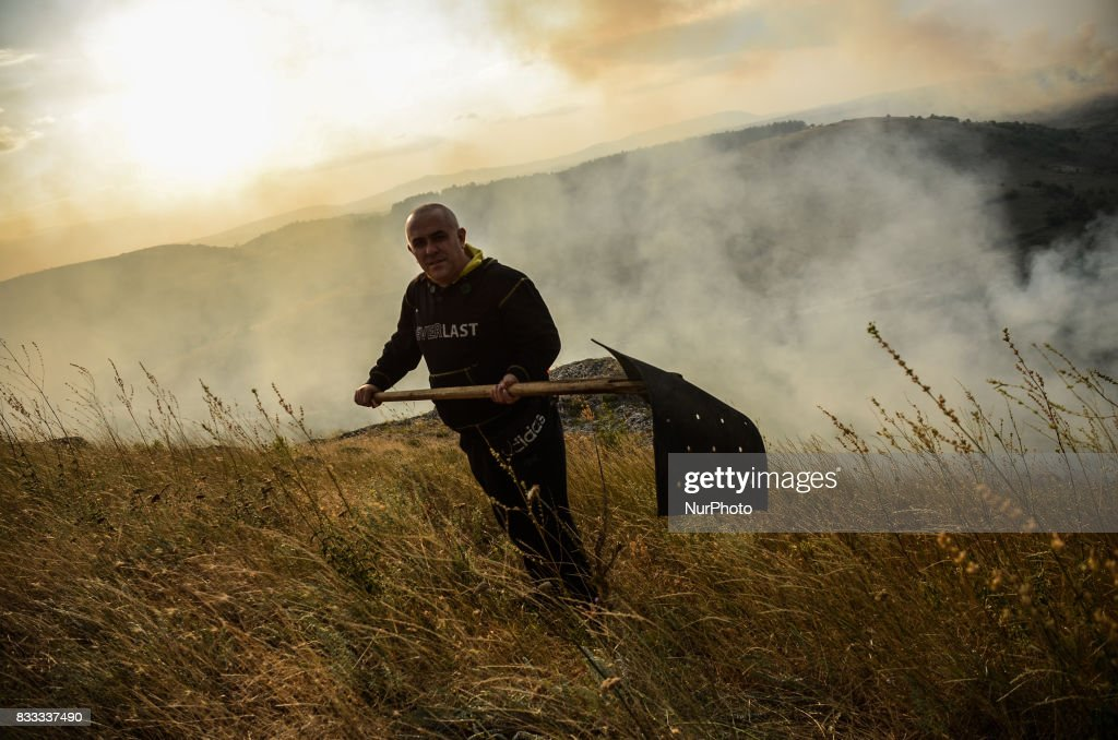 A volunteer is working on the place of the fire near the village of Matochina. Fire destroyed near 2000 acres between the villages of Sakartsi and Matochina, which are located along the Bulgarian-Turkish border fence and 270 kilometres East the Bulgarian capital of Sofia. More than 50 people, firefighters, volunteers and the people from the villages are working on place, Matochina, Bulgaria on August 16, 2017