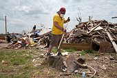 Volunteer Jamie Leahey of New York rakes debris in the ruins of a home on June 18 in Joplin Missouri 'It is good to be here' Leahey said 'It is a lot...