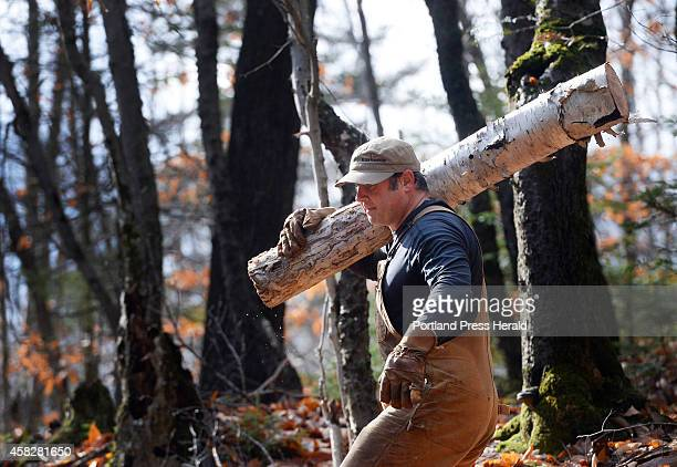 Volunteer Jeff Marcoux of Wakefield NH carries a log off a glades trail at Black Mountain Ski Area in Rumford Sunday October 26 2014