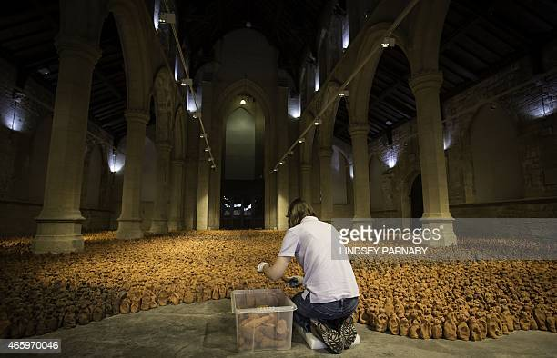 A volunteer lays out sculptures that are part of the installation entitled 'Field for the British Isles' by British artist Antony Gormley in the Nave...