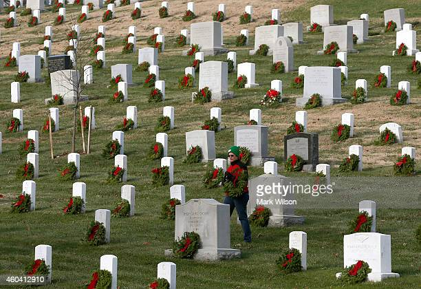 A volunteer looks for a grave to place a wreath on during the National Wreaths Across America Day at Arlington National Cemetery December 13 2014 in...