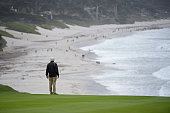 A volunteer looks out on to Carmel beach from the 9th hole during the second round of the Champions Tour Nature Valley First Tee Open at Pebble Beach...