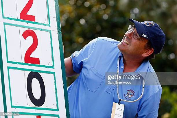 A volunteer looks up to a leaderboard during the second round of the 114th US Open at Pinehurst Resort Country Club Course No 2 on June 13 2014 in...