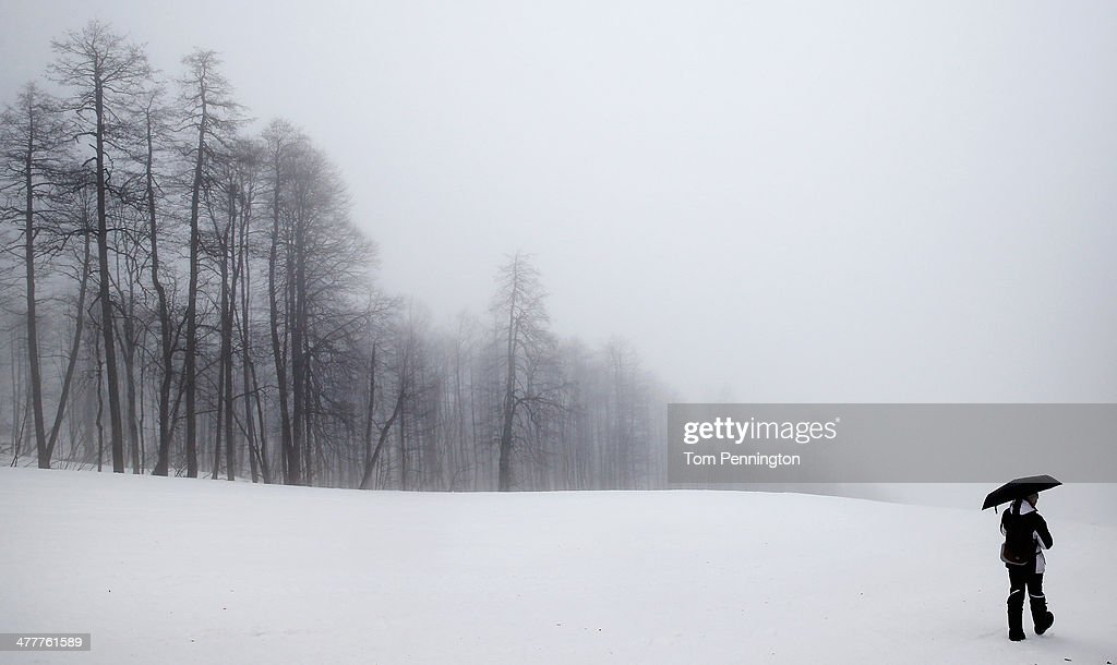 A volunteer makes their way down the course as the first race is delayed due to heavy fog during day four of Sochi 2014 Paralympic Winter Games at Rosa Khutor Alpine Center on March 11, 2014 in Sochi, Russia