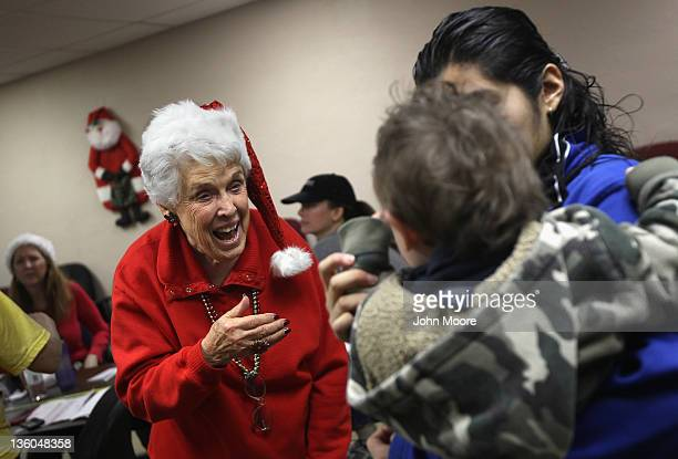 Volunteer Margie Stipes greets an underage mother and her child during a Christmas party for homeless high school students at the Main Place clothing...
