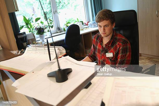 Volunteer Martin Teute mans the reception desk at the FranzJordanStift senior care home on June 21 2012 in Berlin Germany Teute is in his 10th month...