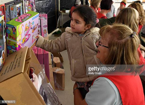 Volunteer Mary Edwards helps Evelin Villa pick out a doll at the 86th annual Denver Santa Claus Shop at the old Kmart store near Evans Ave and Monaco...