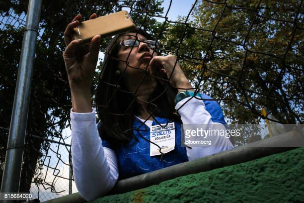 A volunteer medical worker takes a photograph of Henrique Capriles opposition leader and governor of the State of Miranda not pictured as he arrives...