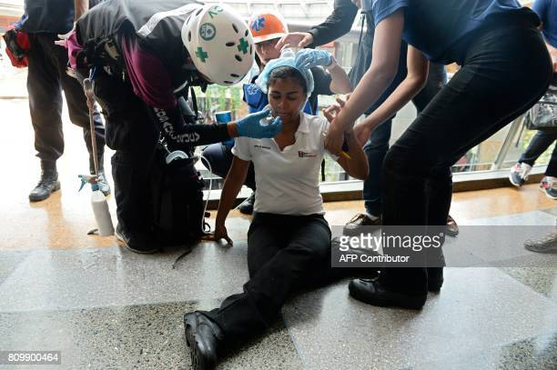 Volunteer medics assist clients and employees of a shopping mall after riot police shot tear gas at opposition demonstrators who took cover inside...
