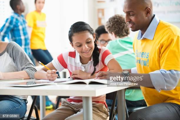 Volunteer mentor helping student with homework