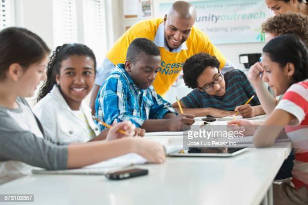 Volunteer mentor helping students with homework