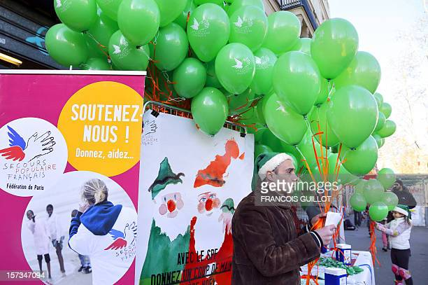 A volunteer of French charity association 'Secours Populaire Francais' sell tickets and green balloons on December 2 2012 in Paris as people with...
