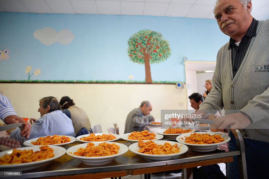 Volunteer of the Caritas 'Catholic charity' carries meals at the soup kitchen of the 'St Benedict parish' in Rome on May 28 2013 As soup kitchens in...