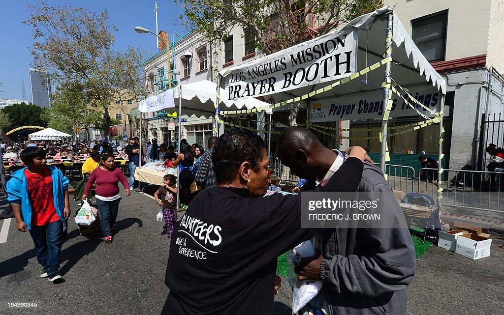 A volunteer offers a prayer to those in need at the Los Angeles Mission's Good Friday event on Skid Row on March 29, 2013 in Los Angeles, California. Celebrities and volunteers joined together in giving something back to this community of the homeless, among the largest in the US, who were fed a fully-prepared meal and had the opportunity to be given foot washing and hygiene kits. Foot washing, a symbolic ritual of humbleness and respect derived from Jesus Christ's washing of his disciples feet at the Last Supper, was offered by the Los Angeles Health Center and volunteers. AFP PHOTO/Frederic J. BROWN