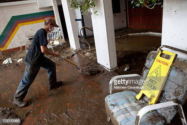 Volunteer Oscar Smith cleans up mud at The Crafts Inn where Tropical Storm Irene caused severe flooding in the town's center on August 31 2011 in...