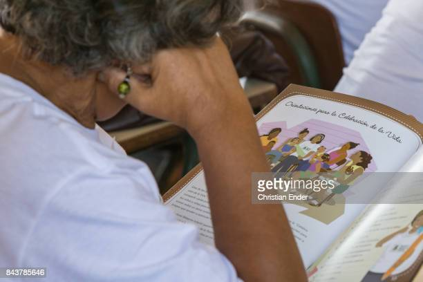 Santo Domingo Dominican Republic December 02 2012 A volunteer participates at a educational lesson reading a book about home visiting for a auxiliary...